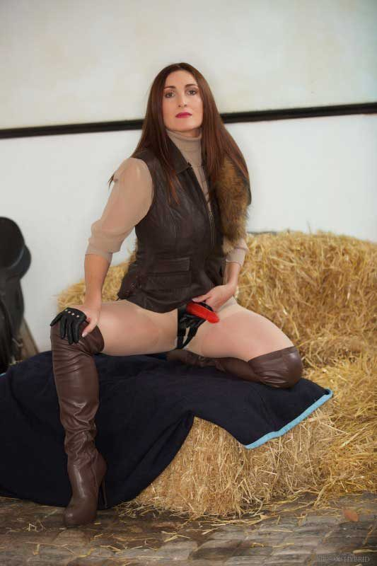 Miss Hybrid strapon and leather thigh boots in the Manor stables.